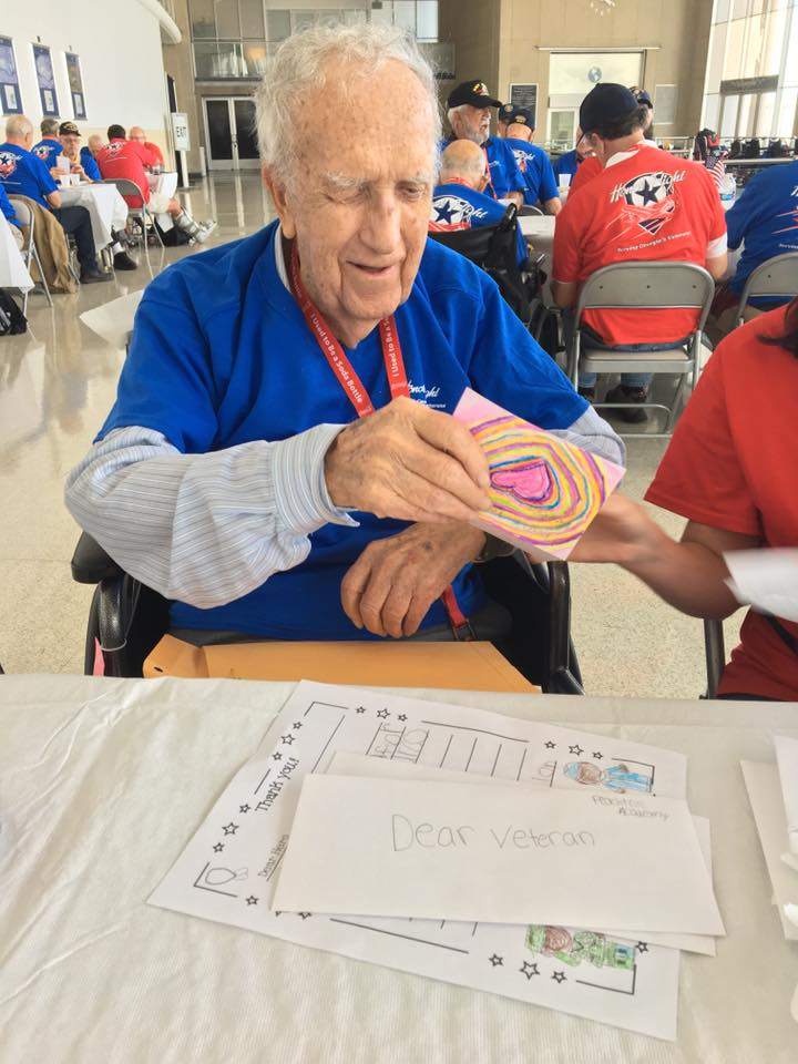 Veteran receiving card from student